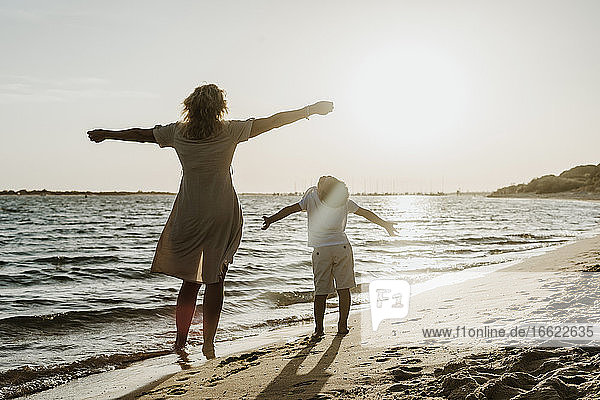 Grandmother and grandson with arms outstretched standing at beach during sunset