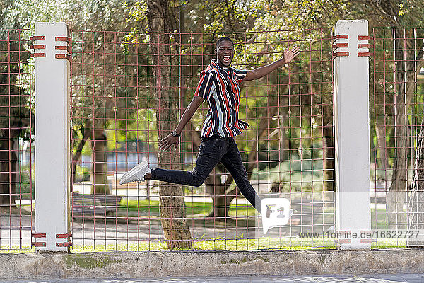 Cheerful young man jumping against fence at park