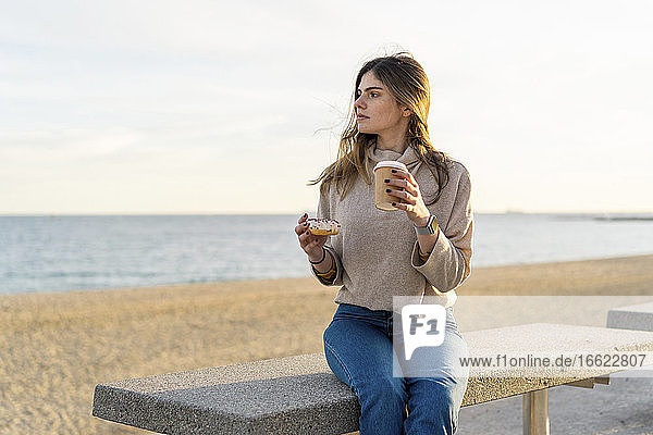 Thoughtful young woman holding fresh donut with disposable cup while sitting on bench at beach and looking away during sunset