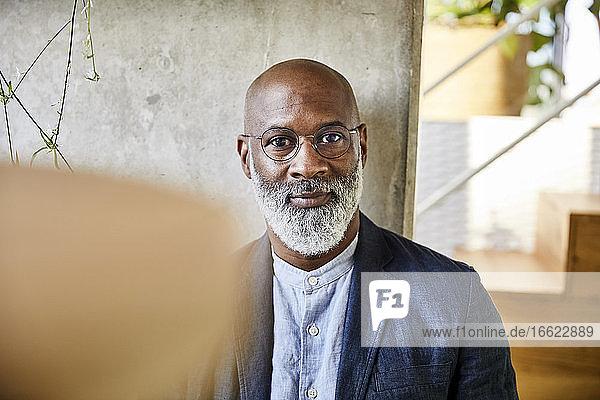 Mature man wearing eyeglasses sitting at home