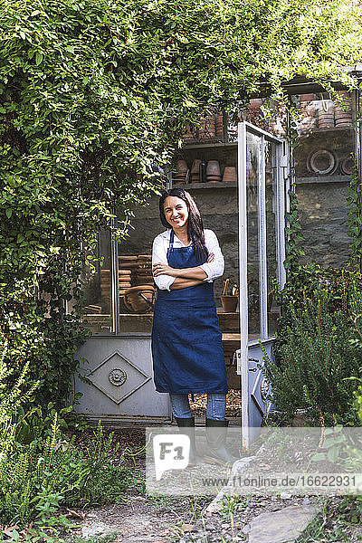 Mature woman with arms crossed standing in back yard