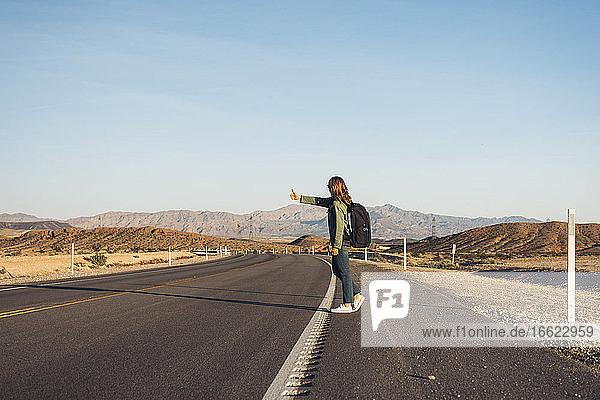 Woman hitchhiking on desert road  Nevada  USA