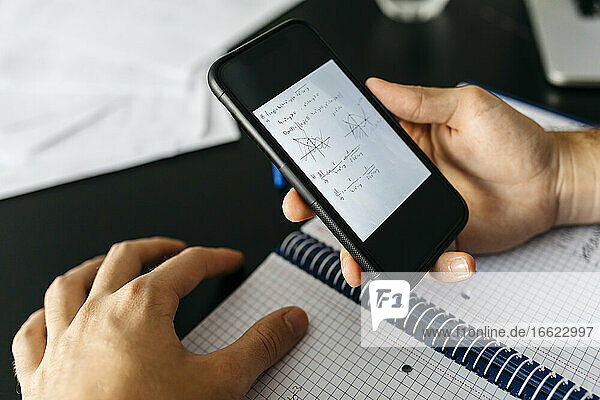 Hands of male adult student holding smart phone with mathematical equation at home