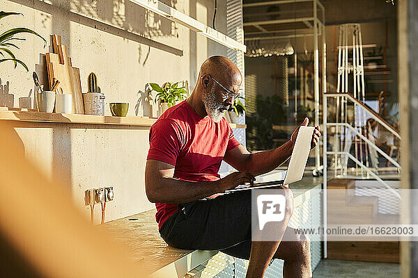 Businessman concentrating on work while using laptop at home