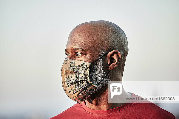 Bald man wearing protective face mask at rooftop against sky during pandemic