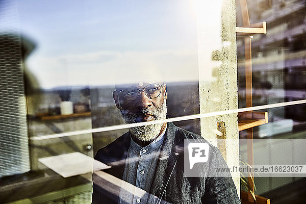 Reflection of mature mature man looking out of window while standing at home