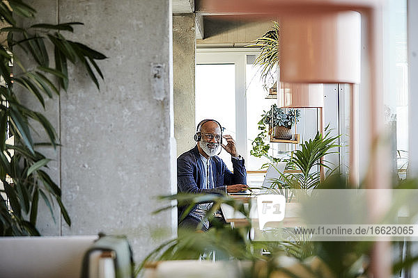 Smiling businessman listening through headphones while sitting with laptop at table and working from home