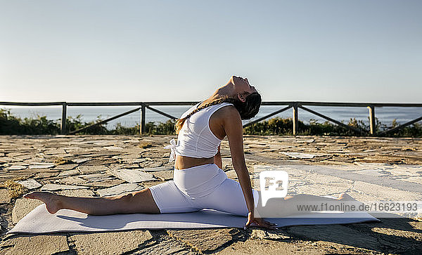 Young woman doing splits on exercise mat against clear sky during sunset