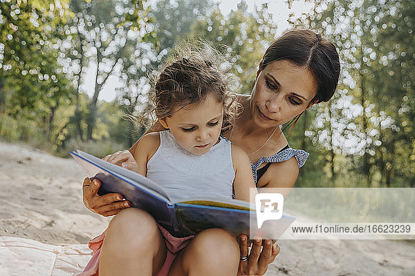 Mother and daughter reading book while sitting at beach
