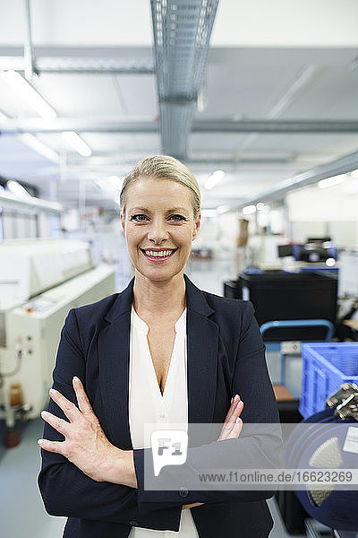Smiling mature blond female professional standing with arms crossed at illuminated industry