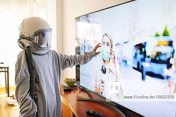 Boy wearing space helmet touching journalist mother on TV at home