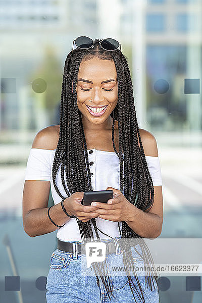 Woman using mobile phone while standing against glass wall in city