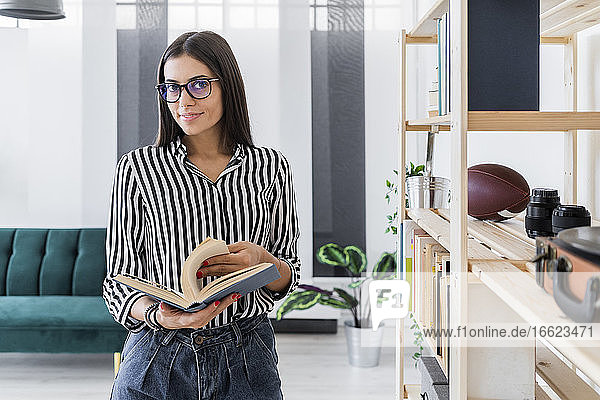 Confident beautiful young design professional holding book while standing by rack at creative office