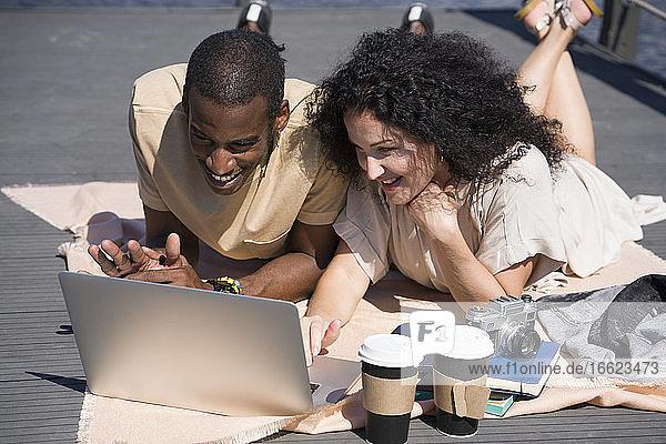 Pärchen mit Laptop auf einem Brückenweg in der Stadt Pärchen mit Laptop auf einem Brückenweg in der Stadt