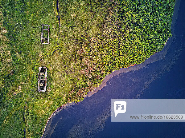 Drone shot of old buildings on green land by Novgorodskaya bay at Primorsky region  Russia