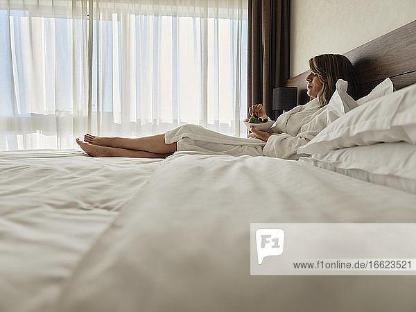Ältere Frau isst frisches Obst und entspannt sich auf dem Bett im Hotelzimmer Ältere Frau isst frisches Obst und entspannt sich auf dem Bett im Hotelzimmer