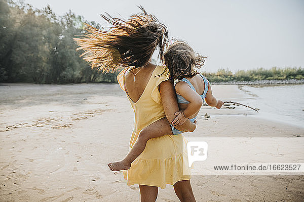 Mother and daughter looking at view while standing at beach