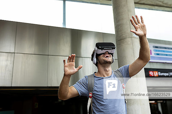 Smiling young male commuter enjoying virtual reality headset at subway station