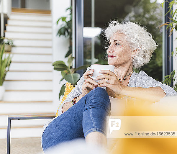 Mature woman drinking coffee while looking away sitting on couch at home