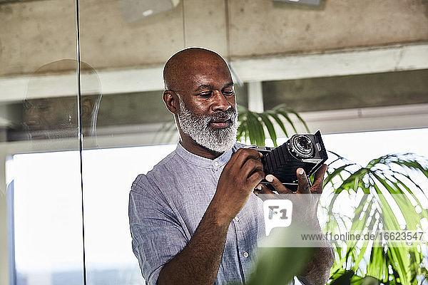Mature man using digital camera while standing at home