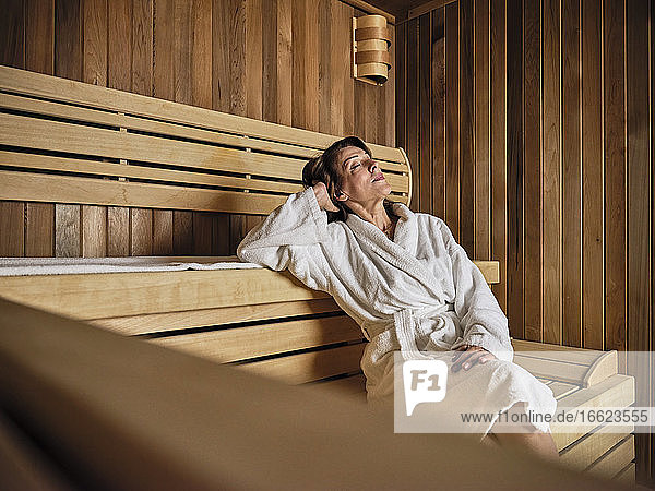 Senior woman with hands behind head relaxing in sauna at health spa