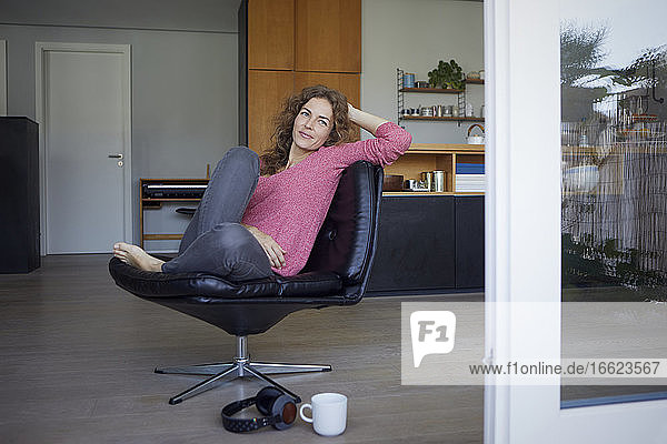 Woman with head in hands sitting on chair at home