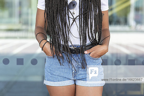 Young woman with hands in pockets standing against glass wall in city