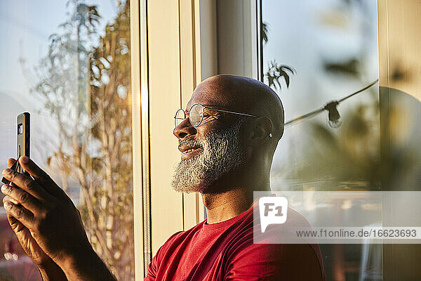 Smiling bearded mature man using smart phone for photographing sunset from terrace