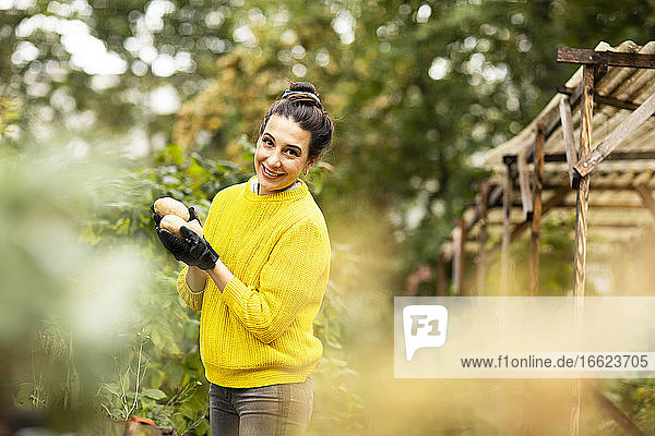 Smiling woman holding vegetable while standing at urban garden