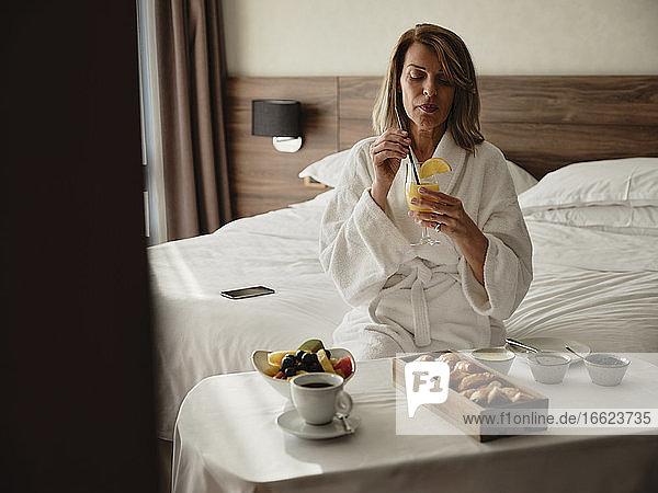 Blonde ältere Frau im Ruhestand trinkt Saft beim Frühstück im Hotelzimmer Blonde ältere Frau im Ruhestand trinkt Saft beim Frühstück im Hotelzimmer