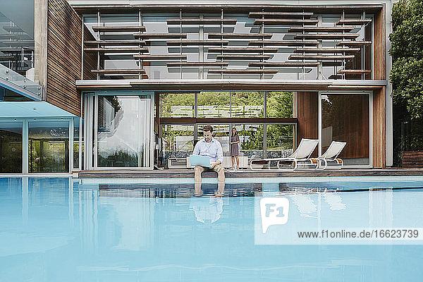 Reifer Mann benutzt Laptop  während er an einem modernen Haus in der Nähe des Pools sitzt Reifer Mann benutzt Laptop, während er an einem modernen Haus in der Nähe des Pools sitzt