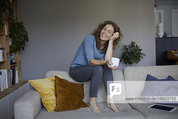 Smiling woman drinking coffee while sitting on top of sofa at home