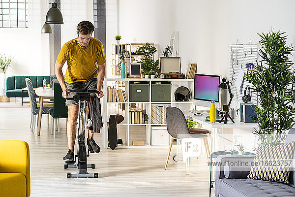 Young man looking down while cycling on exercise equipment at home