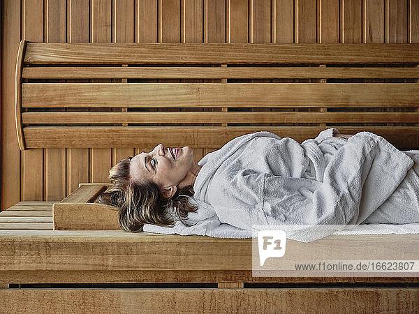 Senior woman reclining on wooden sauna at health spa