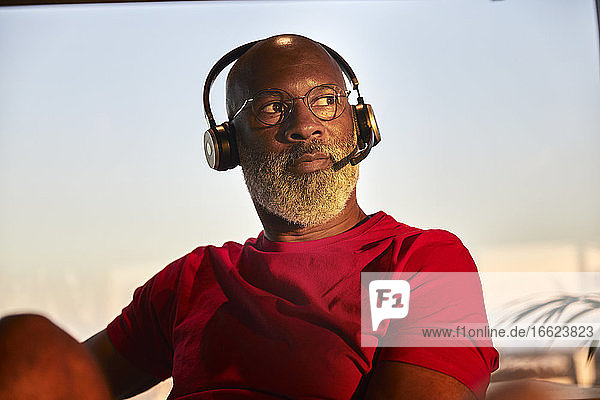 Thoughtful bald man listening through headphones while looking away against sky during sunset
