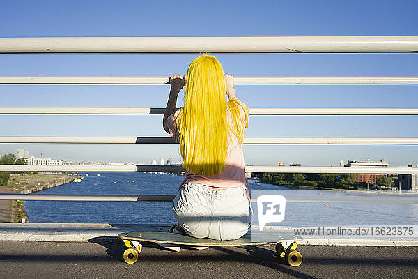 Long hair woman looking at sea while sitting on skateboard during sunny day