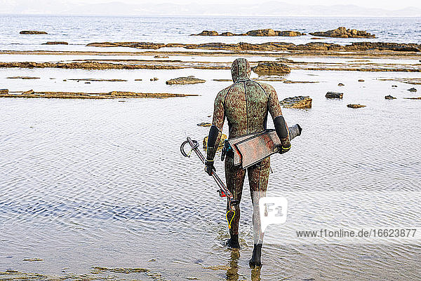Mature man with harpoon and flipper walking at beach