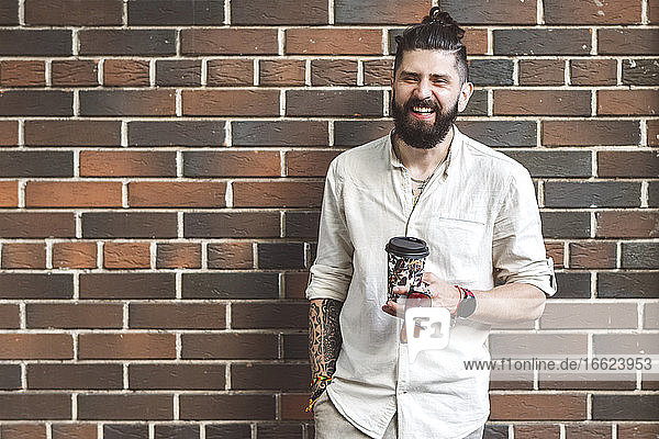 Happy hipster man holding disposable cup while standing against brick wall