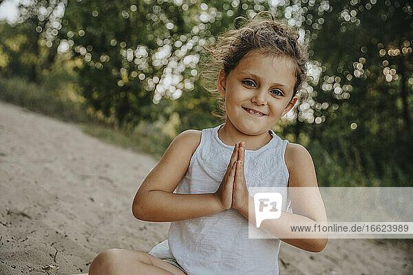 Cute little girl meditating at beach