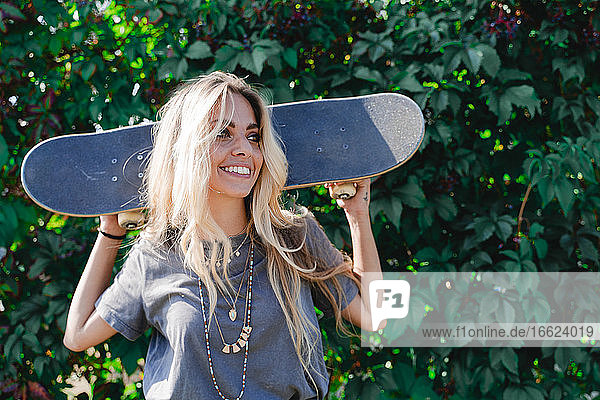 Smiling blond woman holding skateboard while looking away against green plant