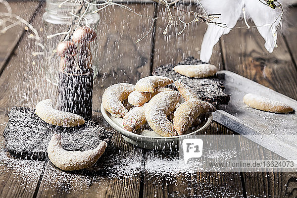 Plate of freshly baked almond cookies with vanilla and powdered sugar
