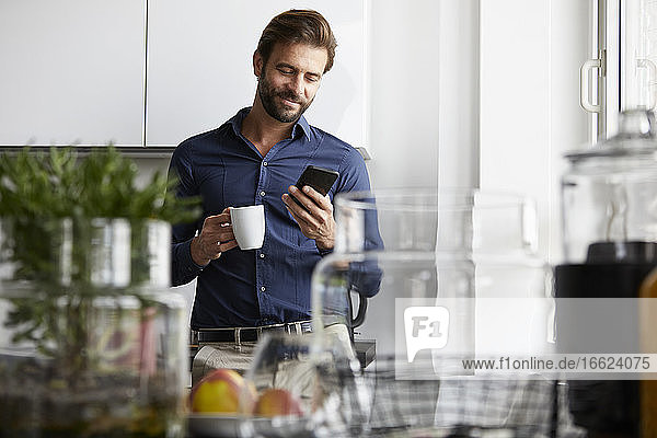 Businessman using mobile phone while drinking coffee at cafeteria