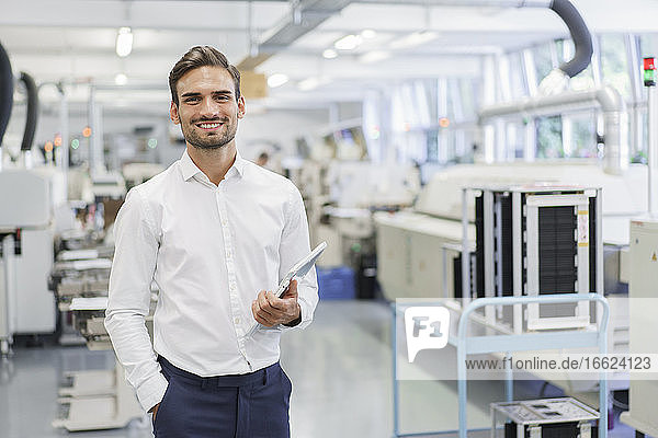 Smiling confident young businessman holding digital tablet while standing with hands in pockets at illuminated factory