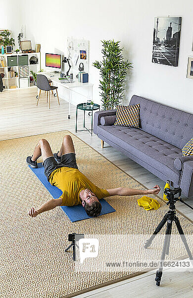 Young man lying on mat while live streaming exercise at home