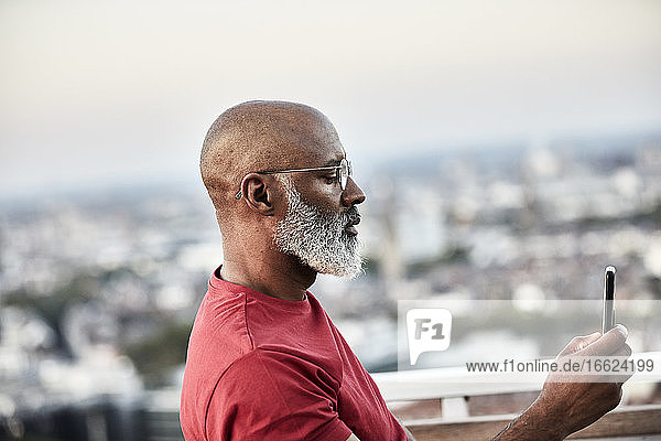 Mature bald man with white beard using smart phone for photographing sunset from rooftop