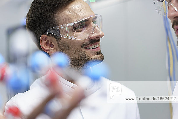 Smiling male scientist holding molecular structure while looking at colleague in illuminated laboratory