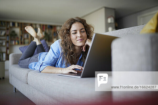 Smiling woman using laptop while lying on sofa at home