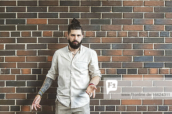 Hipster man gesturing while standing against brick wall
