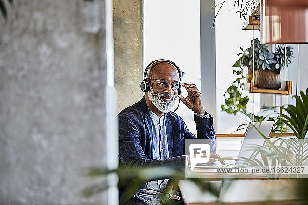 Mature businessman listening through headphones while sitting with laptop at table and working from home