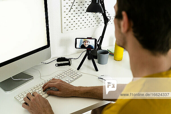 Young man talking on video call while working on computer at home